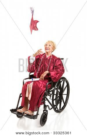 Disabled senior woman graduating college, tosses her cap in the air.  Full body isolated on white.