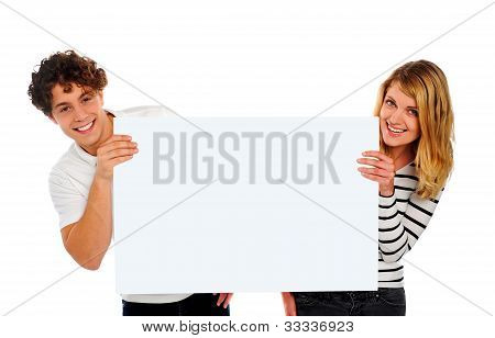 Attractive Smiling Couple Holding A Blank Whiteboard