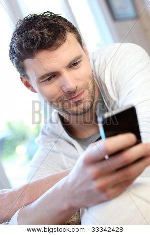 Jovem usando o celular para enviar mensagens curtas