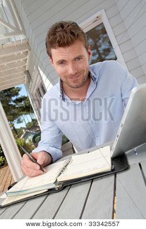 Portrait of smiling man working at home on tablet