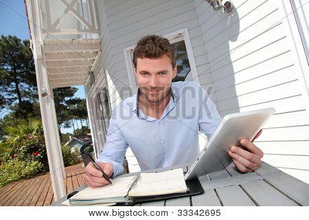 Retrato de hombre sonriente, trabajar en casa en tableta