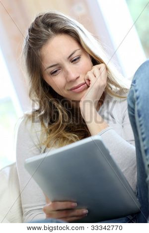 Young woman looking at electronic tablet with puzzled look