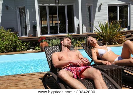 Couple suntanning in long chairs