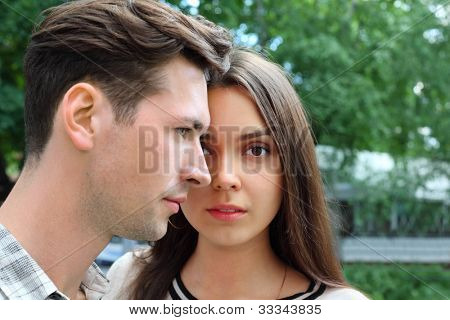 Beautiful pensive man and woman stand in park; green trees; focus on woman
