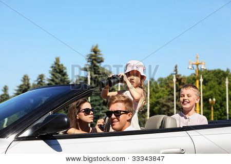 Beautiful father, mother and two children ride in convertible car and play spies