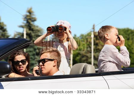Young father, mother and two children ride in convertible car and play spies