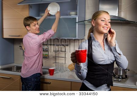 Young man washing dishes and his girlfriend talking by mobile phone in kitchen