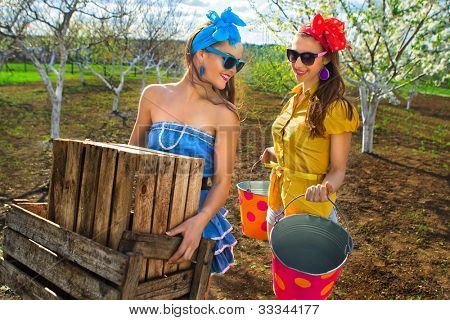 Two young females with wooden box and buckets on garden