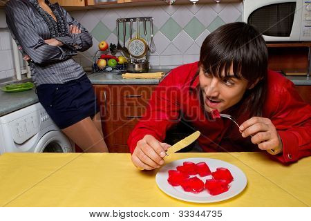 Young man eating red jelly hearts on kitchen