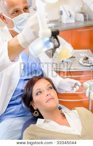 Woman patient at dental surgery with male hygienist stomatology clinic