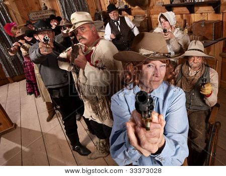 Group Of Cowboys Point Guns In Bar