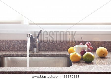 Cup, Fruits And Faucet On The Kitchen
