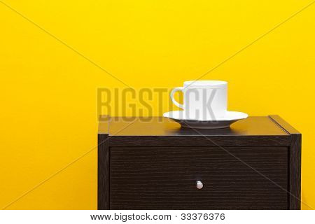 Bedside Table And Cup Against A Yellow Wall In The Apartment