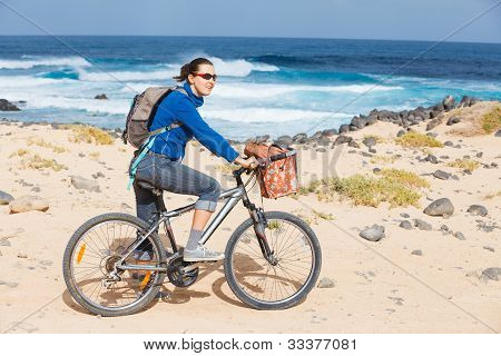 Woman riding bike on a beach