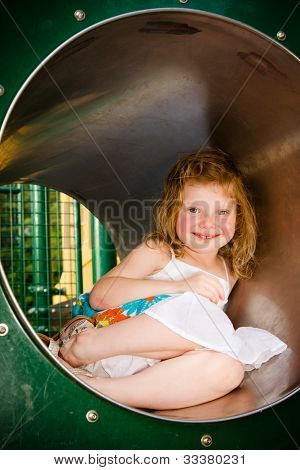 Cute little girl playing in tunnel on playground