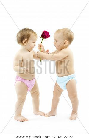 Baby Boy Present Rose Flower To A Baby Girl. Children Wear Colorful Diapers: Pink And Blue