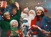 Merry Christmas and Happy Holidays! Grandma, grandpa, mum, dad and children having fun near tree ind poster