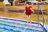 Happy Little Girl In A Red Vest Swimming In The Pool Of The Water Park. Child Learns To Swim. Teachi poster