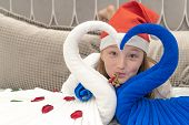 Happy Teenager Girl In Santa Claus Hat Smiling. Heart Made Of Towel Swans. New Year And Travel And H poster
