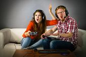Couple Enjoying Leisure Time By Playing Video Games Together, Man And Woman Being Shocked By Game. poster