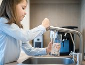 Portrait Of A Little Caucasian Girl Gaining A Glass Of Tap Clean Water. Kitchen Faucet. Cute Curly K poster