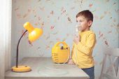 Health Care Concept Of Sick Little Caucasian Boy In Yellow Shirt Holding Inhaler Near His Face Breat poster