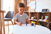 Beautiful toddler boy playing with figurine army soldiers at kindergarten poster