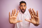 Young indian man wearing casual shirt standing over isolated pink background afraid and terrified wi poster