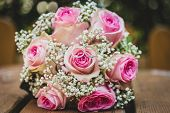 Wedding Bouquet With Pink Roses On Wooden Table With Rings. poster