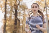 Female Jogger Running On Road And Street In Park With Trees. Woman In Jogging Trail In The Morning.  poster