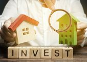 Wooden Blocks With The Word Invest And Houses In The Hands Of A Businessman. The Concept Of Investin poster