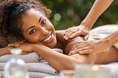 Happy woman relaxing with oil massage on her back at spa resort. Portrait of young african woman rec poster