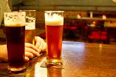 Three Glasses With Beer On A Table In A Bar, Filtered Beer, Dark Beer And Copper Beer. Meeting With  poster