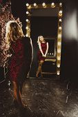 Beautiful Blonde Girl Looks In The Makeup Mirror. Vertical Full Length Rearview Shot Of A Young Blon poster