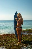 Surfer Girl With Surfboard At The Beach. Young Sexy Woman With Long Blond Hair Wearing Black Bikini. poster
