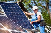 Professional Technician Installing Heavy Solar Photo Voltaic Panel To High Metal Platform On Blue Sk poster