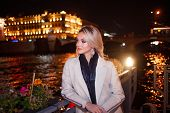 Stylish And Elegant Young Woman In A Beige Coat On The City Waterfront. Night City In Autumn. Portra poster