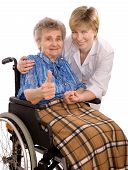 picture of crippled  - Health care worker and elderly woman in wheelchair giving thumbs - JPG