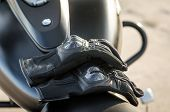 Motorcyclist Gloves On A Motorcycle Seat Against A Motorcycle Fuel Tank Background Close Up poster