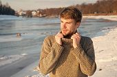 Man Unshaven Handsome Hipster In Knitwear Sweater High Collar Stand Frozen River Background. Winter  poster