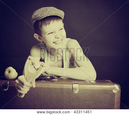 vintage art portrait of liitle boy looking at camera holding catapult and  leaning on old suitcase, retro stylization of 30-50s, toned
