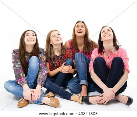 happy young women sitting together smiling and looking up, over white background