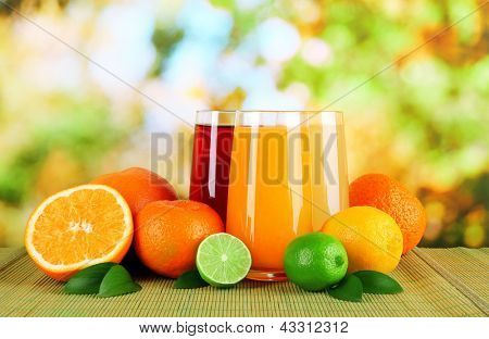 Glasses of juise with leafs and fruits on table on bright background