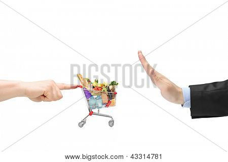 Finger pushing a shopping cart with food products and male hand gesturing stop