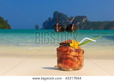 Coconut cocktail with drinking straw on the beach