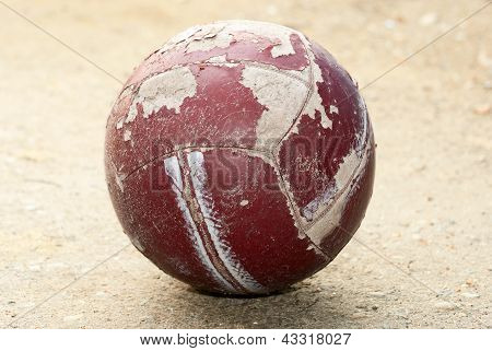 Old worn soccer ball lying on the ground