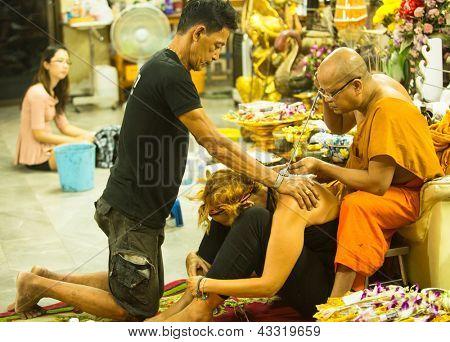 NAKHON CHAI, Tailândia - 1 de MAR: Monge não identificado faz Yantra tradicional tatuagem em 1 de março de 2012, eu