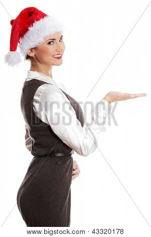 Christmas woman showing copyspace for product with open palm. Young smiling businesswoman with red santa hat. Isolated on perfect white background.