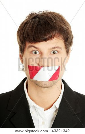 Freedom of speech concept. Young handsome businessman with red and white tape on his mouth. Isolated on white