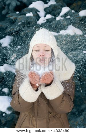 Young Woman Blowing Snow